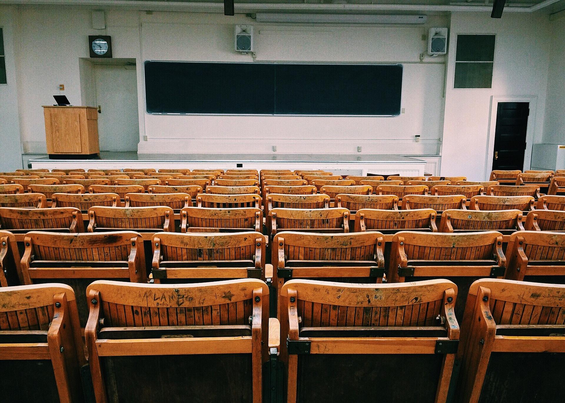 Imagen de un auditorio vacio, con sillas de madera y un tablero al fondo.  Xpirience Day 2020